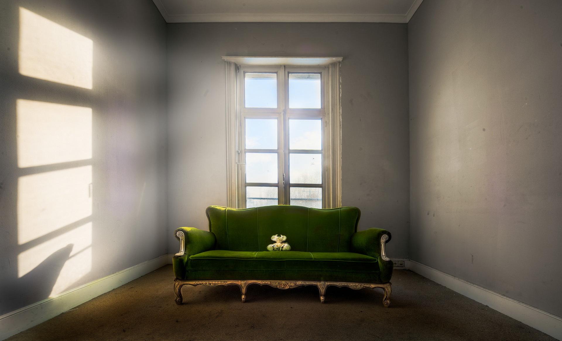 Зеленый диван в пустой комнате