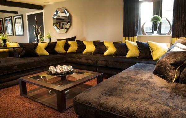 Коричневый кожаный диван в интерьере гостиной добавляет особой роскоши
