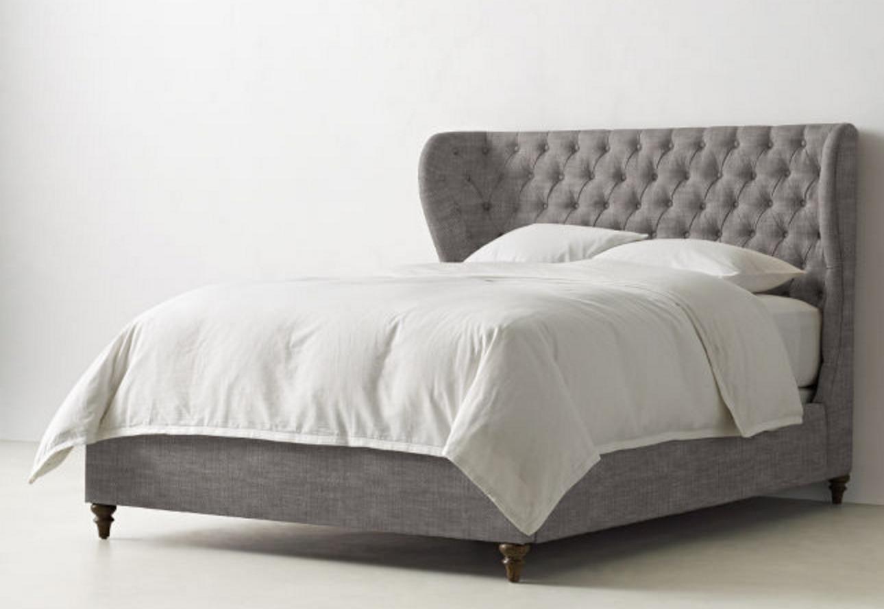 Серая деревянная кровать на ножках с высоким мягким изголовьем